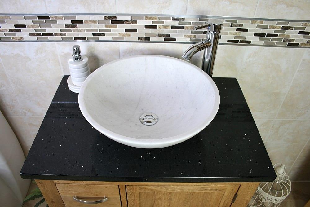 Above View of Oval White Ceramic Basin on Black Quartz Top Vanity Unit