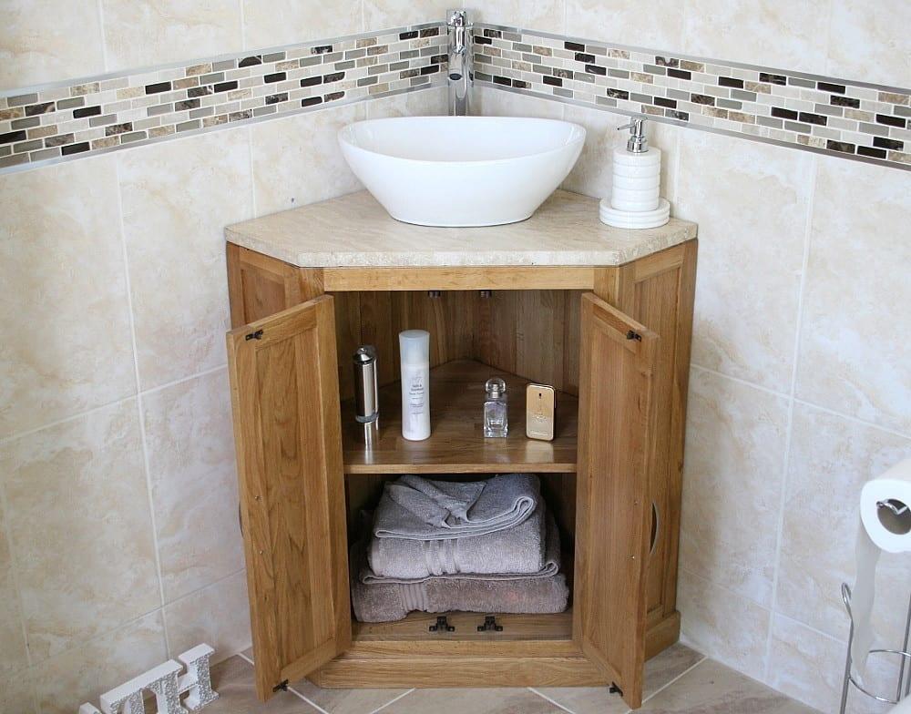 Oval Ceramic Wash Basin on Travertine Top Vanity Unit in Corner Showing Storage